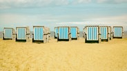Mehrere verschlossene Strandkörbe an einem Strand. © MacRein / photocase.de Foto: MacRein / photocase.de