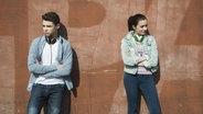 Ein junger Mann und eine junge Frau stehen an einer Wand und schauen in unterschiedliche Richtungen. © imago/Westend61 Fotograf: Westend61