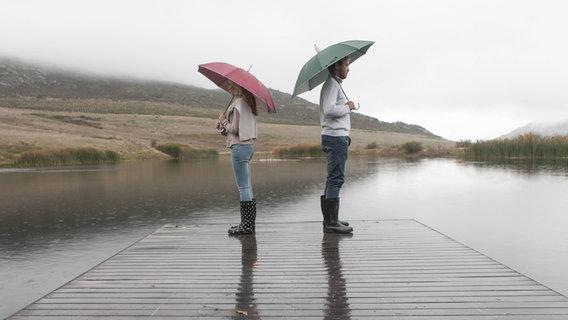 Ein Mann und eine Frau stehen Rücken an Rücken mit Regenschirmen auf einem Steg am See. © imago/Westend61 Foto: Westend61