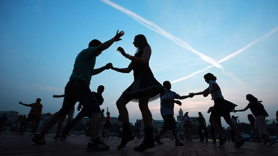 Mehrere junge Menschen tanzen in der Dämmerung im Freien. © picture alliance / dpa Foto: Sergei Fadeichev