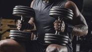Das Bild zeigt einen Sportler beim Gewichtheben. © imago / westend61 Fotograf: Westend61