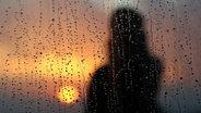Eine Silhouette im Sonnenuntergang hinter einem nassen Fenster. © picture alliance / Mohammed Saber/EPA/dpa Fotograf: Mohammed Saber