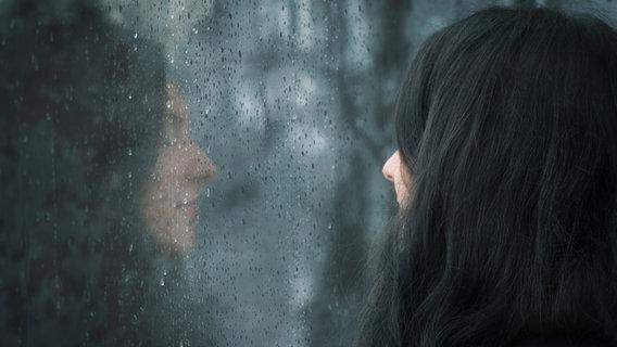 Eine Frau schaut durch ein nasses Fenster. © YesPhotographers / photocase.de Foto: YesPhotographers