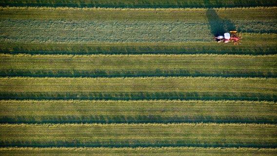 Zu sehen ist ein Acker aus der Vogelperspektive, über den ein Traktor fährt © BeneA / photocase.de Foto: BeneA