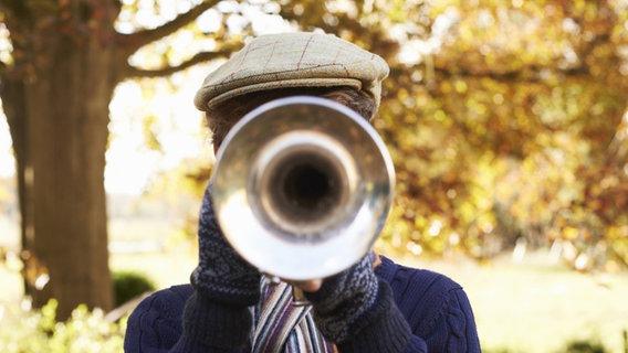 Ein Junge spielt Trompete. Sein Gesicht ist von der Trompete verdeckt. © imago/Science Photo Library Foto: Science Photo Library