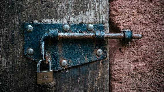 Eine alte Tür mit einem Vorhängeschloss. © picture alliance/Jan Haas Foto: Jan Haas
