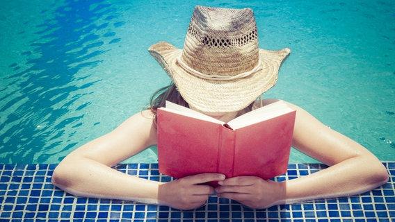 Eine Frau mit einem Sonnenhut steht im Wasser und liest ein Buch. © imago/Westend61 Foto: Westend61