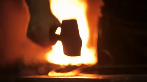 Eine Hand hält etwas in einen Schmiedeofen. © NDR