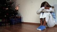 Ein Mädchen kauert traurig neben dem Weihnachtsbaum. © imago/emil umdorf Fotograf: emil umdorf