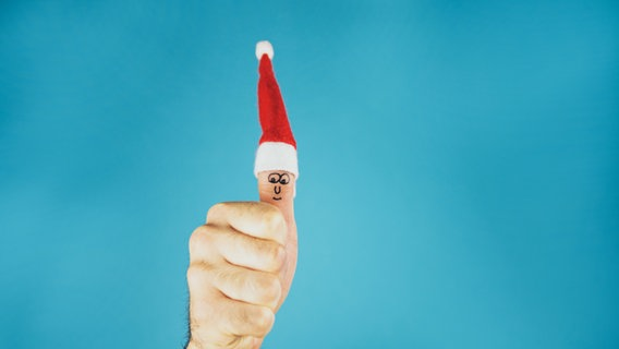 Daumen hoch mit einer Weihnachtsmütze auf dem Daumen. © David-W- / photocase.de Foto: David-W- / photocase.de