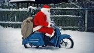 Ein Weihnachtsmann fährt auf einer Vespa durch den Schnee. © photocase