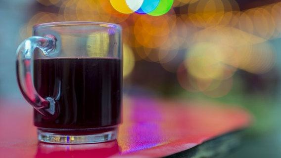 Ein gefülltes Glühweinglas steht auf einem Tisch. © imago/Westend61 Foto: Westend61