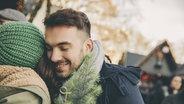 Zwei Menschen umarmen sich auf dem Weihnachtsmarkt. © imago/Westend61 Foto: Westend61