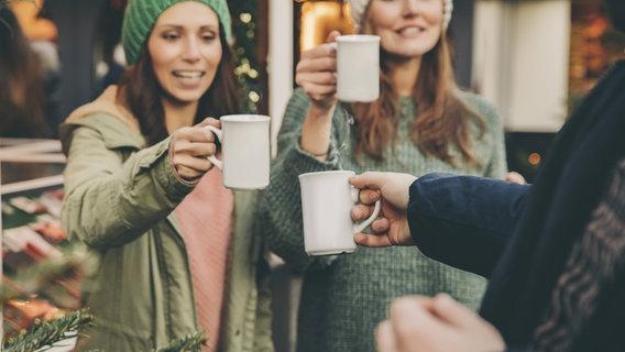 Junge Menschen stoßen auf dem Weihnachtsmarkt miteinander an. © imago/Westend61 Foto: Westend61