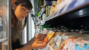 Eine Frau sieht sich ein Produkt im Kühlregal an. © imago stock&people