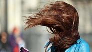 Windböen wehen einer Frau die Haare ins Gesicht © dpa Fotograf: Oliver Berg dpa/lnw