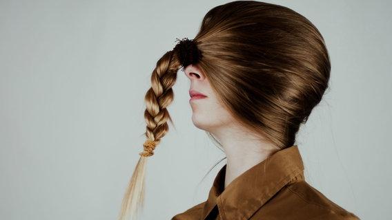 Eine Frau hat ihre Haare in Zopfform vor die Augen gebunden. © Nanduu / photocase.de Foto: Nanduu
