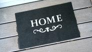 """Eine Fußmatte mit der Aufschrift """"Home"""". © picture alliance / R. Goldmann Fotograf: Ralph Goldmann"""