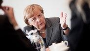 Angela Merkel im Interview. Gesprächspartner unscharf im Anschnitt. © dpa bildfunk