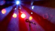 Ein Mikrofon auf einem Ständer, im Hintergrund rote und blaue Bühnenbeleuchtung. © Picture Alliance Foto: Britta Pedersen