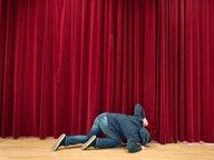 Mann kniet auf der Büühne und spitzelt unter dem Vorhang durch. © .marqs / photocase.de Fotograf: .marqs