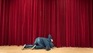 Mann kniet auf der Büühne und spitzelt unter dem Vorhang durch. © .marqs / photocase.de Foto: .marqs