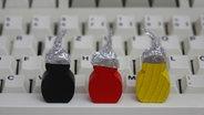 Drei Holzfiguren mit Aluhüten stehen auf einer Tastatur. © picture alliance / ZB Foto: Sascha Steinach