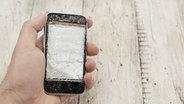 Eine Hand hält ein Smartphone mit gesplittertem Bildschirm. © imago/Westend61