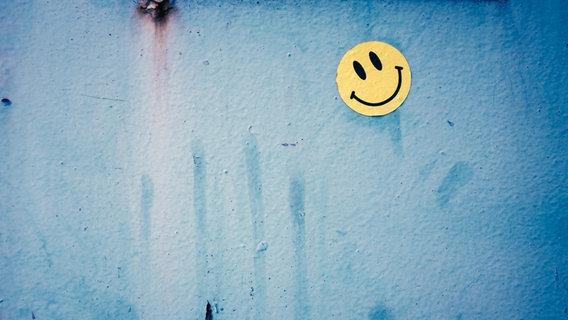 Ein lächelndes gelbes Smiley ist an eine blaue Wand geklebt. © suze / photocase.de Foto: suze / photocase.de
