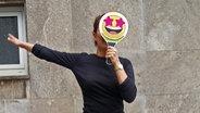 Eine Frau mit Emoji vor dem Gesicht springt in die Luft. © N-JOY Foto: Eva Köhler