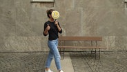 Eine Frau mit Emoji vor dem Gesicht springt in die Luft. © N-JOY Fotograf: Eva Köhler