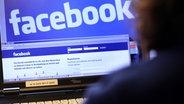 Eine Frau schreibt an einem Laptop auf der Website des sozialen Internet-Netzwerkes Facebook. © dpa
