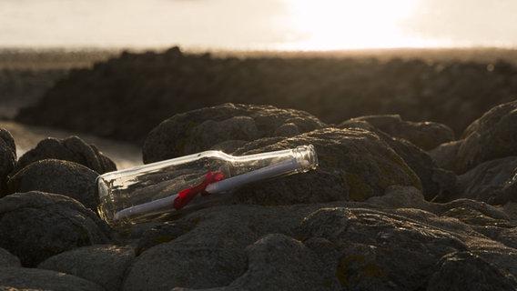 Flaschenpost liegt auf Steinen am Strand. © Imago/Westend61 Foto: Imago/Westend61