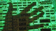 Der Schatten einer Hand schwebt über einer Computerplatine © picture-allicane/JOKER Fotograf: Alexander Stein