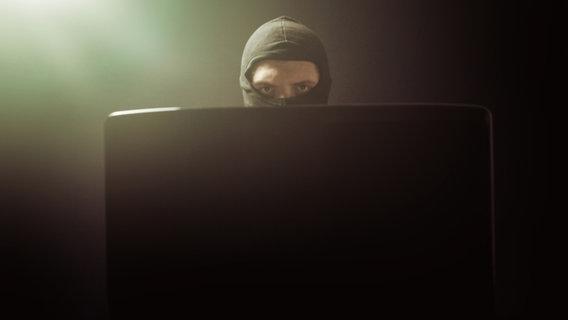 Ein Mann mit einer Maske hinter einem Laptop-Bildschirm. © Brilliant Eye / photocase.de Foto: Brilliant Eye / photocase.de
