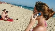Bild zeigt eine Frau, die mit ihrem Handy im Urlaub telefoniert. © picture-alliance.com
