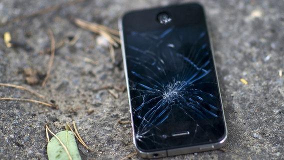 Ein defektes Mobiltelefon liegt am Boden © picture alliance / dpa