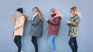 Das Bild zeigt vier junge Frauen, die auf ihr Smartphone starren. © imago / Westend61 Fotograf: Westend61