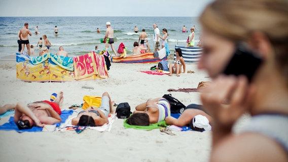 Frau telefoniert mit Handy am Strand © dpa