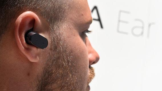 Das Bild zeigt einen Mann mit Bluetooh-Kopfhörer im Ohr. © picture alliance / dpa Foto: Rainer Jensen
