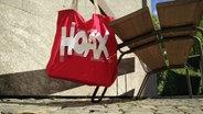 """Tasche mit dem aufgeklebten Wort """"Hoax"""" hängt an einer Bank. © N-JOY Fotograf: Eva Köhler"""