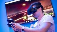 Ein Besucher der GamesCom trägt die VR-Brille HTC Vive © picture alliance / Marius Becker/dpa Foto: Marius Becker