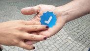 Eine Hand übergibt einen blauen Haken. © N-JOY Fotograf: N-JOY