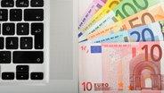 Foto zeigt Laptop-Tastatur mit Geldscheinen
