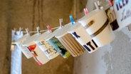 Bemalte Kaffeebecher hängen an einer Wäscheleine © koordinate / photocase.de Fotograf: koordinate