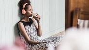 Das Bild zeigt eine Frau, die Musik über Kopfhörer trinkt und dabei einen Kaffee trinkt. © imago/westend61 Fotograf: westend61