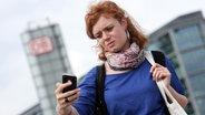 Frau versucht Empfang mit ihrem Handy zu kriegen.  Fotograf: Bodo Marks