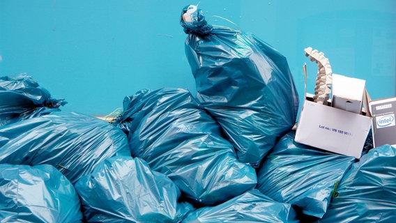 Viele blaue Müllsäcke aufeinandergestapelt, darauf stehen einige Kartons. ©  picture alliance / JOKER Foto:  Karl-Heinz Hick