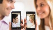 Ein Pärchen hält ein Smartphone mit ihrem Foto hoch. © Bildagentur-online Fotograf: Tetra Images/Bildagentur-online