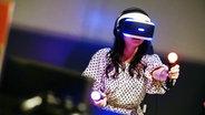 Mädchen trägt die Playstation VR auf einer Spielemesse in Tokio am 1. März. © picture alliance / dpa Fotograf: Christopher Jue